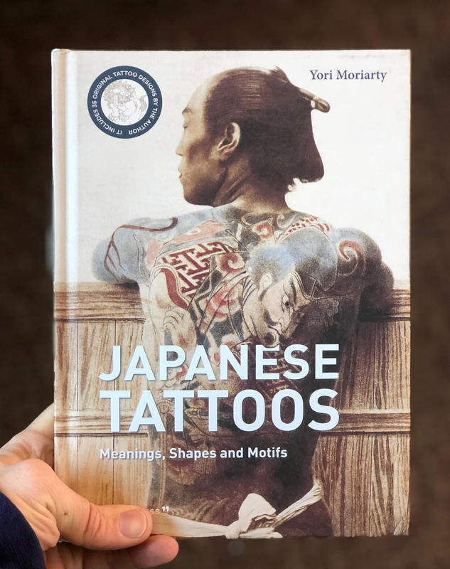 A shirtless japanese man, his back covered in tattoos.
