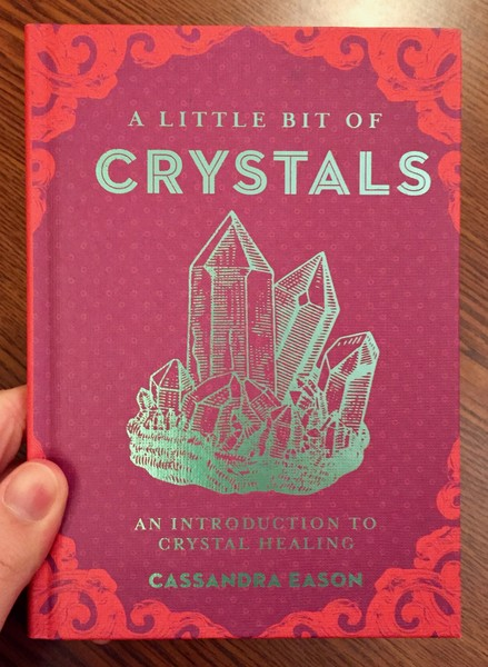 A Little Bit of Crystals: An Introduction to Crystal Healing [A teal crystal shard on a maroon background.]
