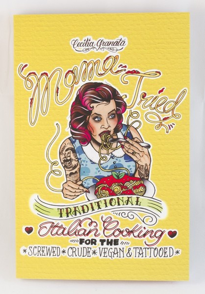 "A tattooed woman eating some good-looking spaghetti and ""meat""balls on the yellow cover of a book"