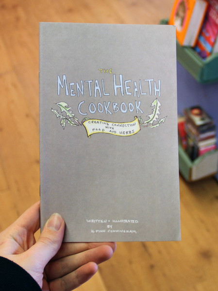 Cover of Mental Health Cookbook: Creating Connections with Food and Herbs which has a couple of drawings of leaves surrounding the title on the otherwise plain cover