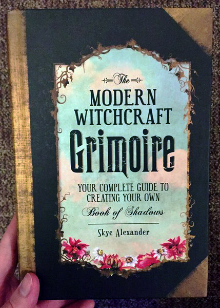 Cover of The Modern Witchcraft Grimoire: Your Complete Guide to Creating Your Own Book of Shadows which features a border of flowers and greenery around the title