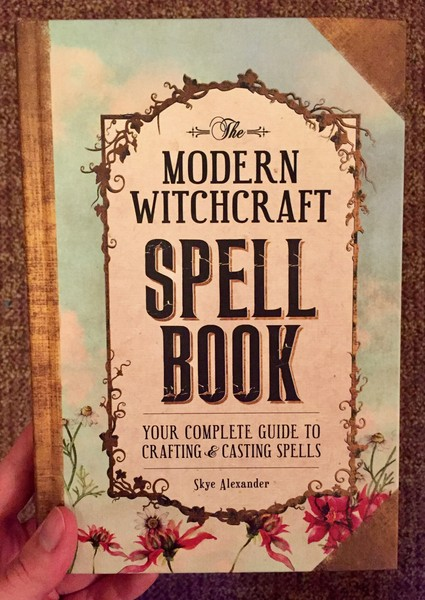 Cover of The Modern Witchcraft Spell Book: Your Complete Guide to Crafting and Casting Spells which features a border of greenery and flowers around the title