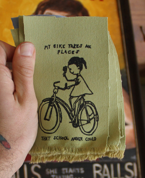 "patch with image of person on a bike with the text ""my bike takes me place that school never could"""