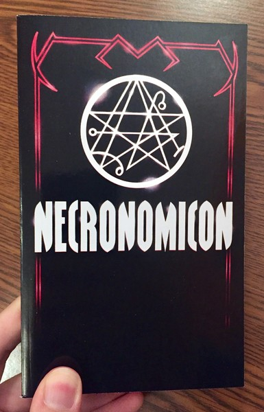 a black paperback with some satanic symbolism
