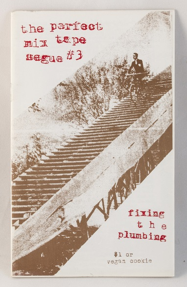 A white zine with an old photo of a person riding a bike down a set of stairs