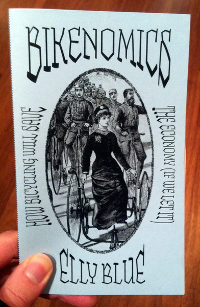 A light blue zine with an illustration of several people of 100 or so years ago cycling down the road. It focuses on a woman in a carriage