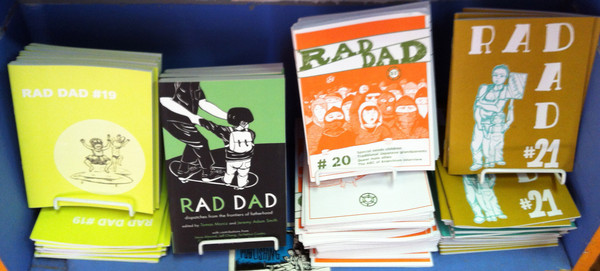 A shelf of Rad Dad zines and the book