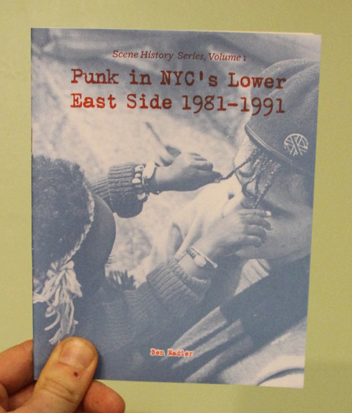 A zine cover with a photo of a child playing with a man's braids