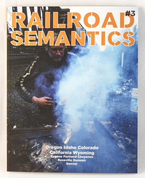 A zine cover with a photo of someone starting a fire by railroad tracks