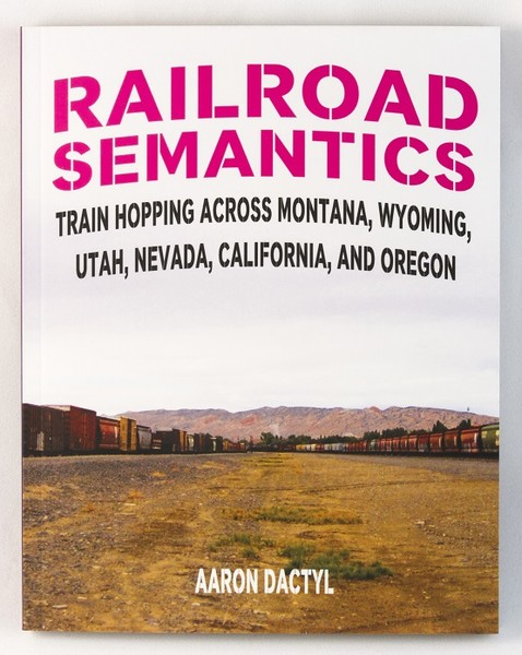 the cover of a book with an image of a train-yard and a mountain in the distance