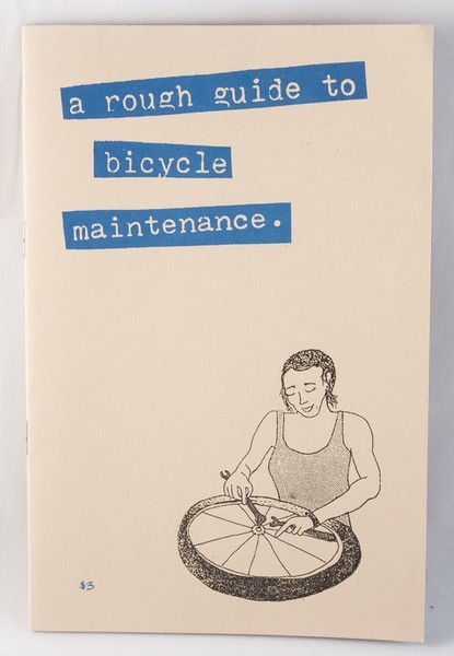 rough guide to bicycle maintenance zine cover with a picture of a woman working on a bike wheel