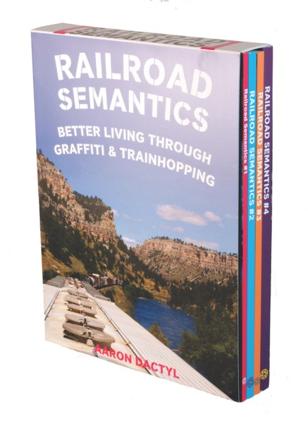 A box of zines! On the cover is a photo of the top of a train on the tracks surrounded by mountains