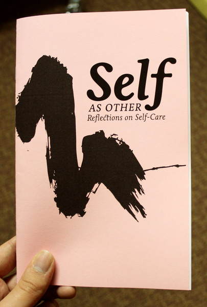 a photo of the Self As Other zine, featuring a plain peach cover with a black swoosh of ink and the title in black.