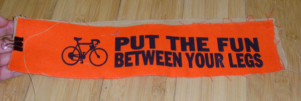 "long patch with bicycle logo and text ""put the fun between your legs"""