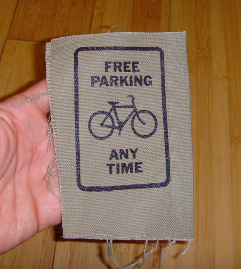a canvas patch that says free parking any time with a drawing of a bicycle