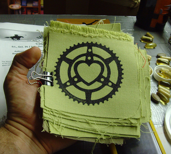 canvas patch printed with the microcosm logo a bicycle chainring heart