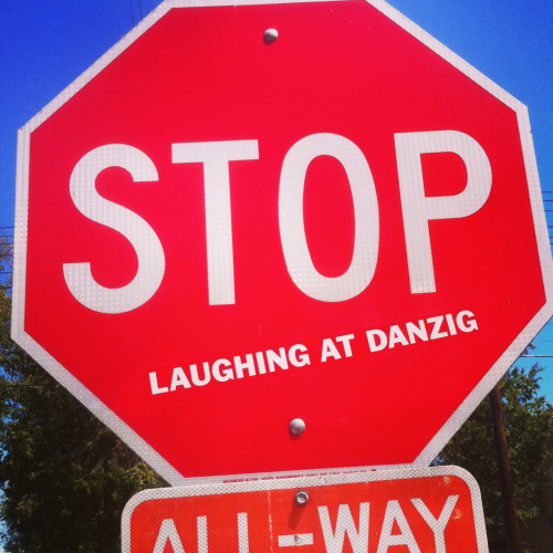 "A stop sign with a ""laughing at danzig"" sticker on it"