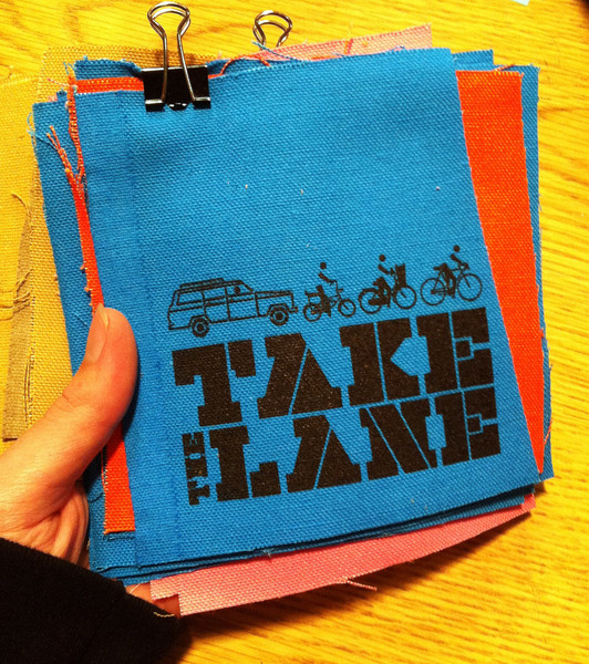 "patch with image of bicycles in traffic with text ""take the lane"""