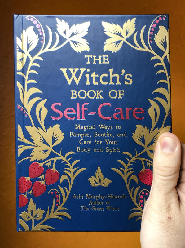 a photo of The Witch's Book of Self Care, with a dark blue cover featuring plant vines and fruit imagery