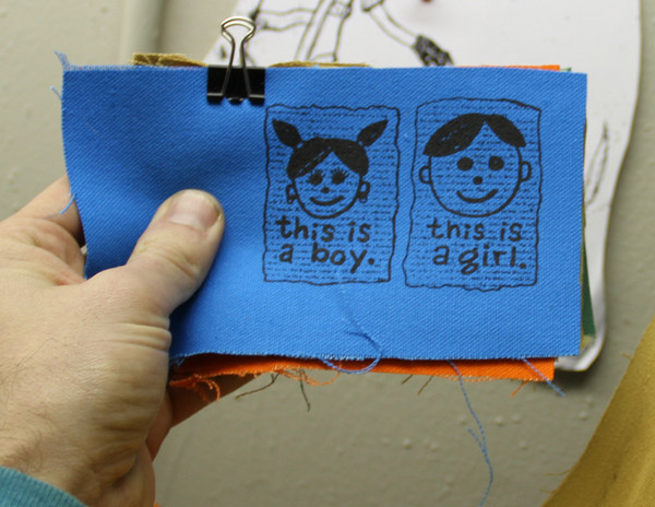 patch with a person with pigtails and earrings sayingthis is a boy and one with a short haircut saying this is a girl