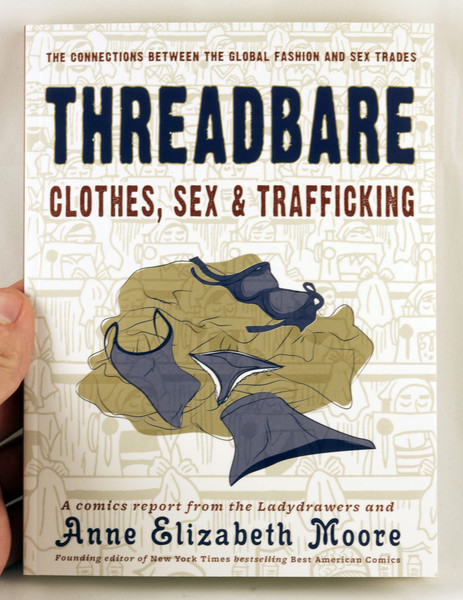 A white book with an illustration of a pile of clothes overlaying on illustrations of sweatshop laborers