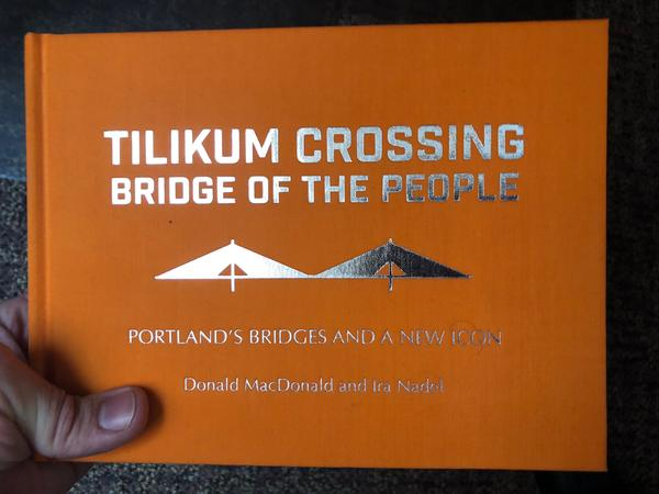 a gold-embossed bridge on an orange hardcover book