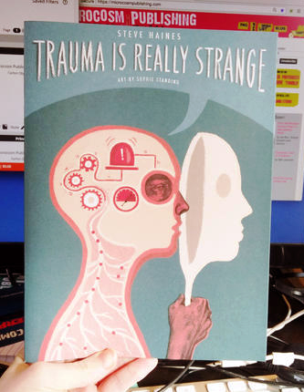 Cover of Trauma is Really Strange which features a human bust in profile holding up a mask over its face. Inside the head, there are gears and alarms.