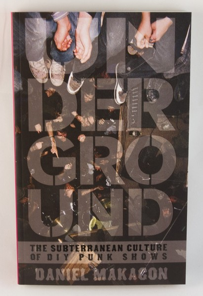A black book cover with a photo of the legs of people sitting on a balcony over the heads of show-goers. The text is transparent