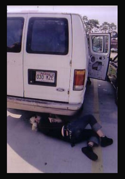 a photo of someone crawling under a van to fix it