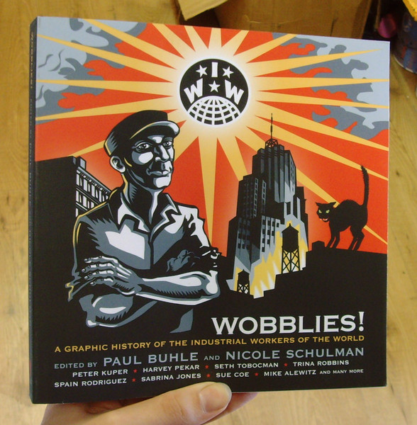 Wobblies Book: A Graphic History - black background with a man in a hat and a bright orange backgroun with clouds at the side - a cat on the left hand side and a bright ball in the center with stars and 'W, W'