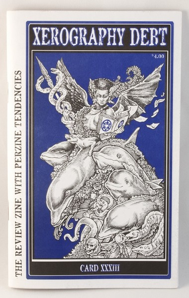 A blue zine with an illustration of a demonic/angelic looking women (with horns and wings) riding on a pile of objects and subjects including a skull and two dolphins