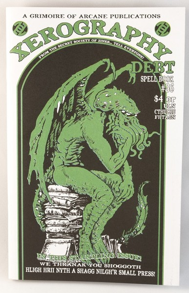a white, black, and green zine with an illustration of a gargoyle-like kraken-looking being, sitting on a stack of books blowup