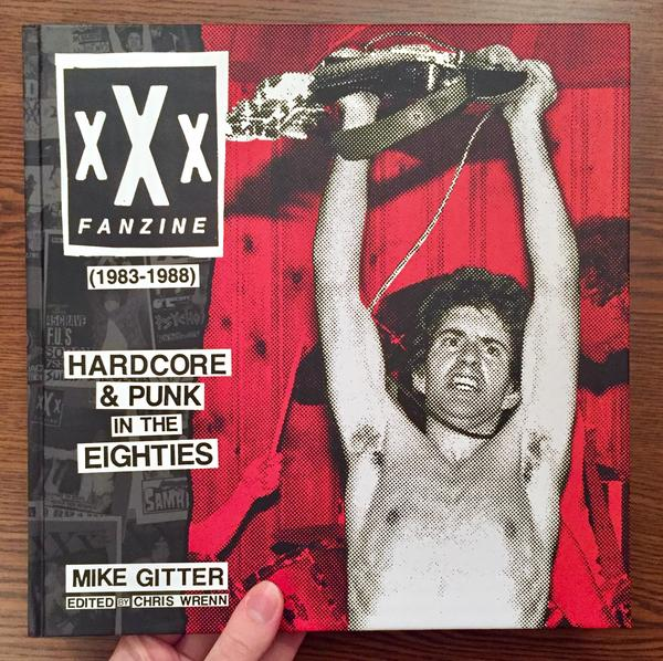 Cover of xXx Fanzine (1983-1988) which features a topless man holding a guitar over his head as if in victory