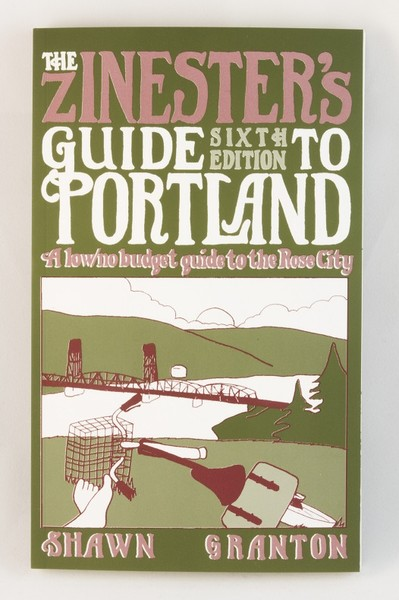 A green zine/small book with an illustration of a cyclist relaxing on a grassy hill, looking over the city of Portland and Hawthorne Bridge